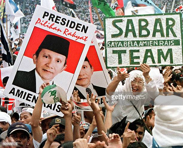 People shout while holding posters reading ' I Defend Amien Rais Team' during the campaign at Bung Karno Stadium in Jakarta 26 June 2004 In front of...
