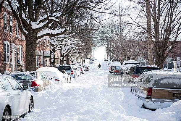 People shovel snow from a covered street following a blizzard on January 25, 2016 in Wilmington, Delaware. Many streets in the city remained covered...