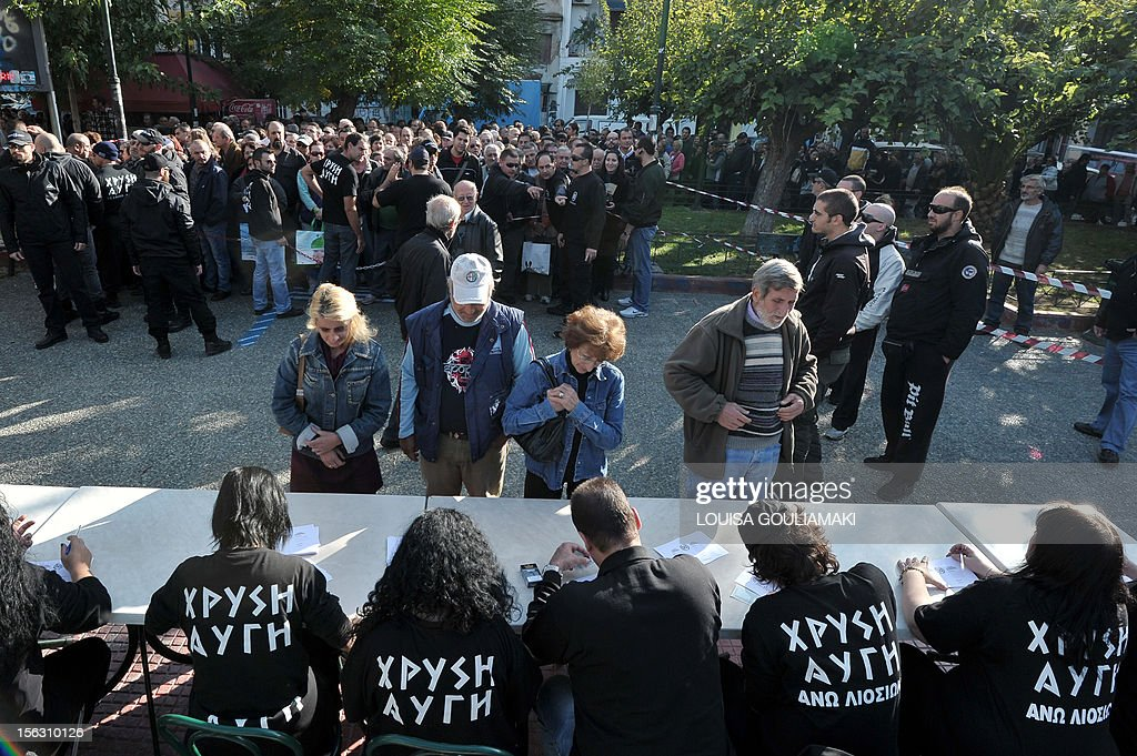 People show their identity card to register for a free food distribution by members of Greece's ultra nationalist party Golden Dawn, dedicated to Greeks citizens only at an Athens square on November 13, 2012.