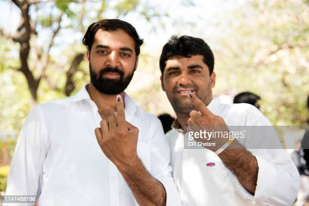 people show their ink-marked fingers after casting their votes. - after stock photos and pictures