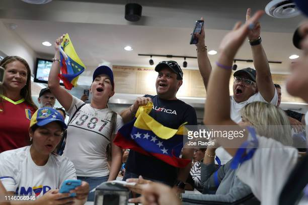 People show their support for the interim Venezuelan President Juan Guaido as they watch events unfold on television at the Venezuelan El Original EL...