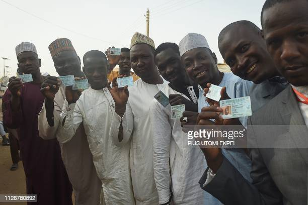 People show they ID cards as they stand in line to vote in Daura Katsina State northwest Nigeria on February 23 2019 Nigerians began voting for a new...