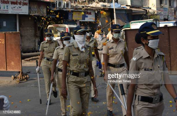 People shower flowers petal on Police personnel wearing PPE Kit during route march at Laljjipada,Kandivali during nationwide lockdown due to COVID -...