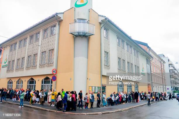 People showing their sympathy to muslims stand outside the mosque at the Islamic Cultural Centre in Oslo on August 11 one day after a gunman armed...