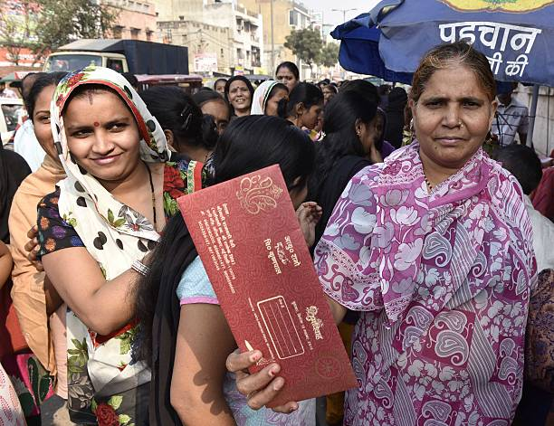 People shows marriage ceremony invitation cards to enter in the Punjab National Bank to exchange their old currency Rs 500 and 1000 at Pahar Ganj on..