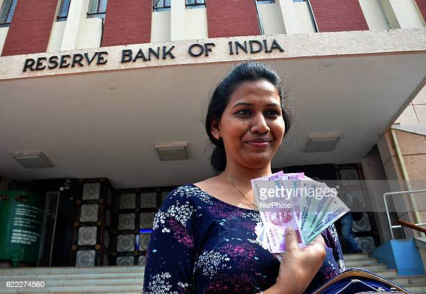 People shows the new 2000 rupees note after get it in exchange discontinued currency notes at the Reserve Bank of India in the eastern Indian city...