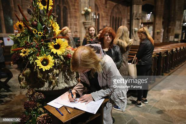 People sign a condolence book after a 'service of reflection' for murdered aid volunteer Alan Henning at Eccles Parish Church on October 5 2014 in...