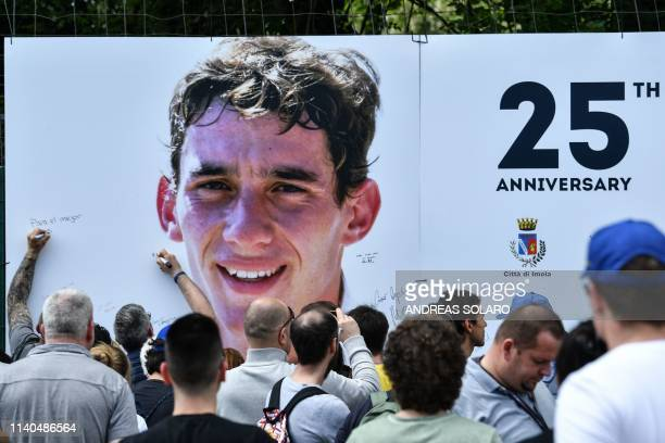 TOPSHOT People sign a giant placard bearing a portrait of Brazilian's F1 driver Ayrton Senna on the Tamburello track curve of the Imola Enzo and Dino...
