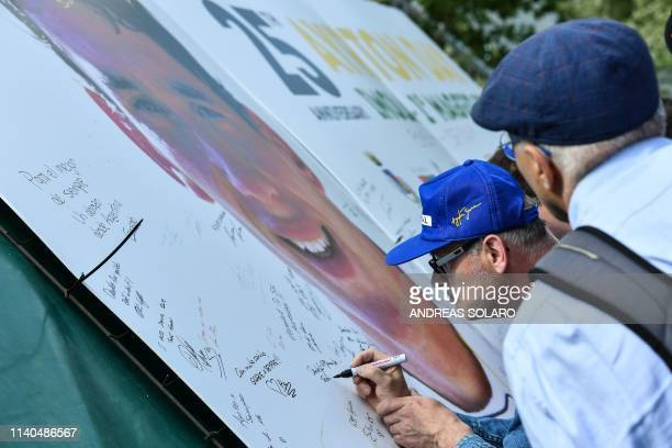 People sign a giant placard bearing a portrait of Brazilian's F1 driver Ayrton Senna on the Tamburello track curve of the Imola Enzo and Dino Ferrari...