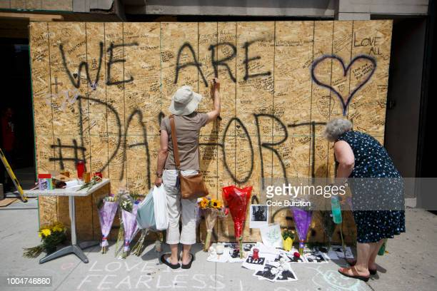 People sign a makeshift memorial on Danforth Ave. Where people are adding flowers and messages to honour and remember the victims of Sunday night's...