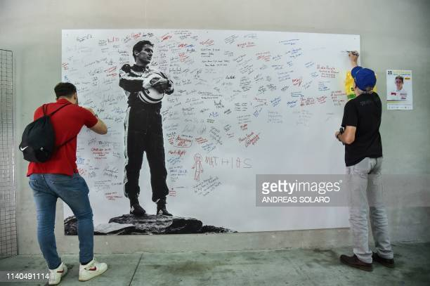 People sign a poster bearing a photo of Brazilian's F1 driver Ayrton Senna during an exhibition as they attend a ceremony marking the 25th...
