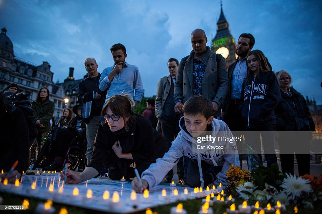 People sign messages of condolence for MP Jo Cox during a vigil in Parliament Square on June 16, 2016 in London, United Kingdom. Jo Cox, 41, Labour MP for Batley and Spen, was shot and stabbed by an attacker at her constituicency today in Birstall, England. A man also suffered slight injuries during the attack. Jo Cox was reportedly shot and stabbed while holding her weekly surgery at Birstall Library, Birstall near Leeds and later diedl. A 52-year old man has been arrested in connection with the crime.