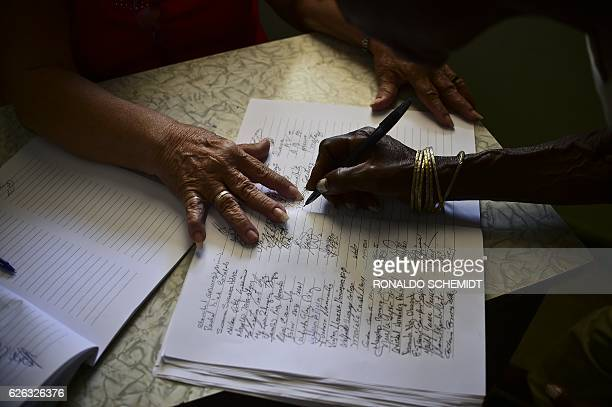 People sign the condolence book in the City Hall of Guanabacoa to pay homage to late Cuban revolutionary leader Fidel Castro in the Guanabacoa...
