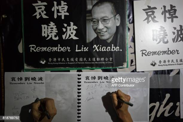 People sign their names at a memorial event for the late Chinese Nobel laureate Liu Xiaobo in Hong Kong on July 19 2017 Hundreds turned out in Hong...