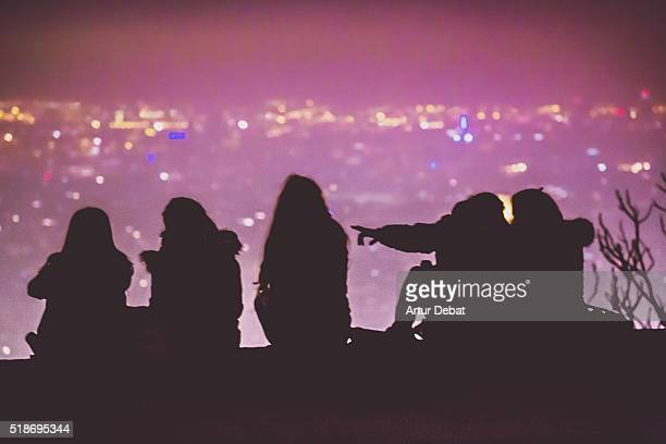 People silhouette by night contemplating the Barcelona city from the bunkers hill viewpoint with the bokeh city lights.