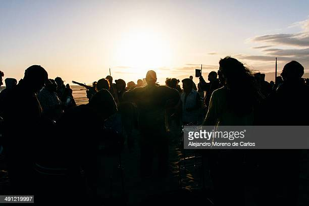 People silhouettes from behind on a music festival on the beach at sunset, Venice Beach, Los Angeles, California, United States.