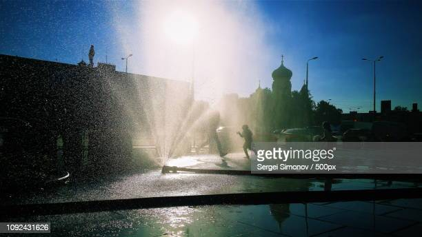 people silhouettes on fountain at hot summer - sergei stock pictures, royalty-free photos & images