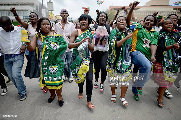 People sing and dance as they gather in Mthatha waiting for the funeral cortege of former South African president Nelson Mandela to pass by on its...