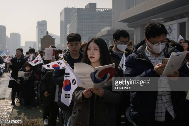 People sing during a ceremony marking the 100th anniversary of the Independence Movement, in the central Gwanghwamun area of Seoul on March 1, 2019....