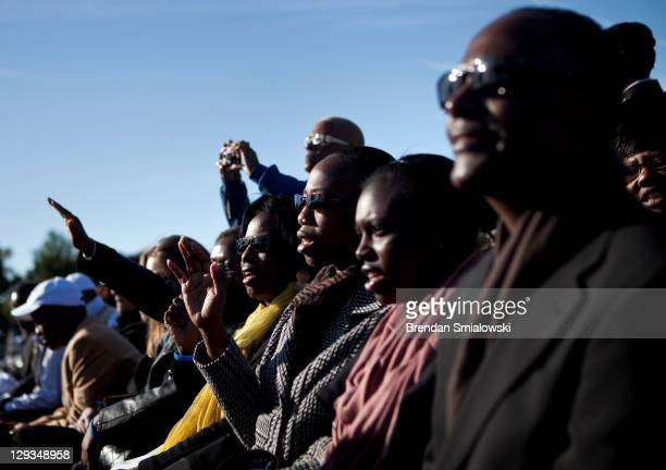 People sing during a dedication ceremony at the Martin Luther King Memorial on the National Mall October 16 2011 in Washington DC President Barack...