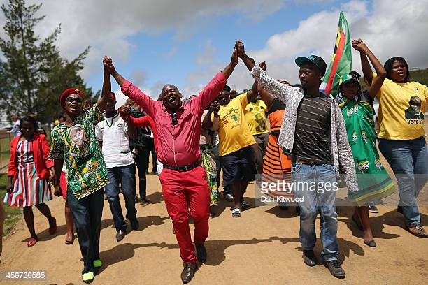 People sing near the former South African President Nelson Mandela's home during his state funeral on December 15 2013 in Qunu South Africa Mr...