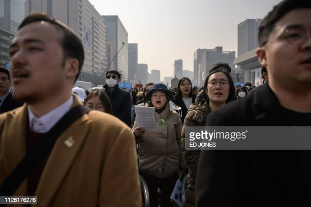 People sing South Korea's national anthem during a ceremony marking the 100th anniversary of the Independence Movement in the central Gwanghwamun...