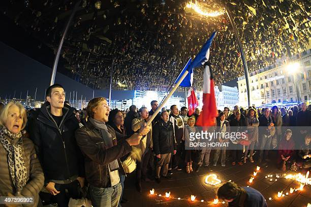 People sing the French national anthem on November 16 2015 on the old Harbour in Marseille as they gather to pay tribute to victims of the November...