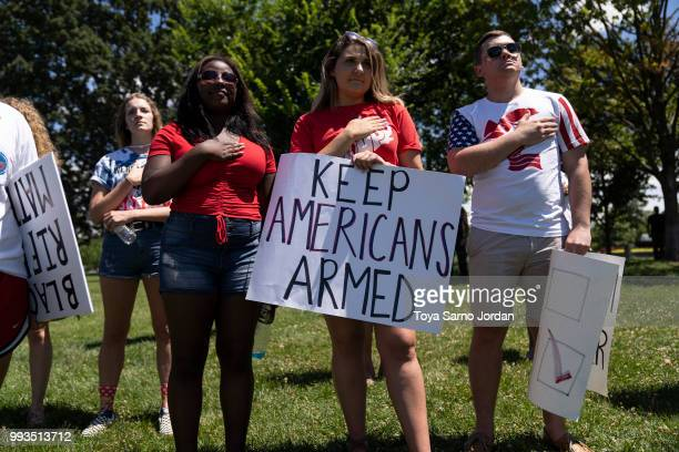 People sing the national anthem during the March For Our Rights rally promoting Second Amendment Rights and the safety of students in schools outside...