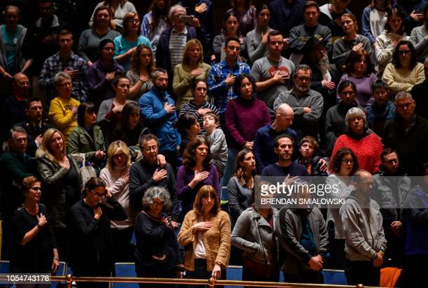 People sing the US national anthem during a vigil to remember the victims of the shooting at the Tree of Life synagogue the day before at the...