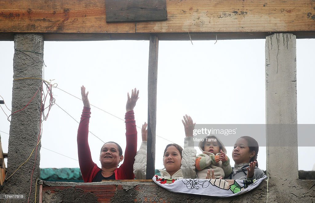 People sing to music being played before Pope Francis arrived in the Varghina favela, or shantytown, on July 25, 2013 in Rio de Janeiro, Brazil. More than 1.5 million pilgrims are expected to join Pope Francis for his visit to the Catholic Church's World Youth Day celebrations. Pope Francis will deliver his welcome address to the celebrations on Copacabana Beach later today as World Youth Day runs July 23-28.