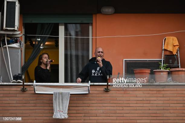 """People sing, wave and clap their hands, during a flash mob """"Una canzone per l'Italia"""" at the Magliana district in Rome on March 15, 2020. - Italy..."""