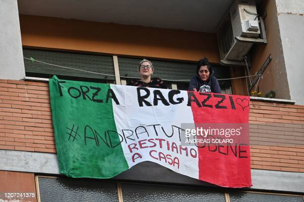 "People sing, wave and clap their hands next to a banner reading ""Forza ragazzi hastag #andratuttobene, restiamo a casa "" , during a flash mob ""Una..."