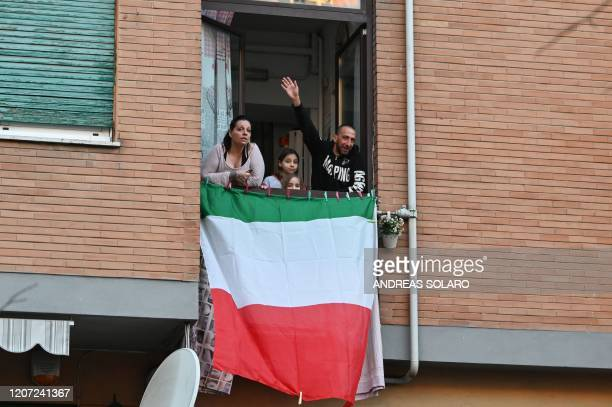 "People sing, wave and clap their hands next to an Italian flag, during a flash mob ""Una canzone per l'Italia"" at the Magliana district in Rome on..."