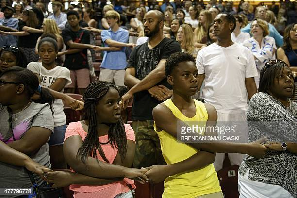 People sing 'We Shall Overcome' during a vigil at TD Arena for victims of the recent church shooting in Charleston South Carolina on June 19 2015 For...