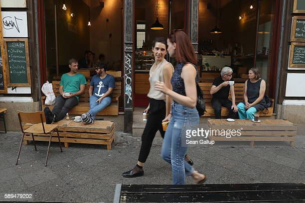 People sip coffee at a cafe in Mariannenstrasse in Kreuzberg district on a warm summer afternoon on August 13 2016 in Berlin Germany While fall and...