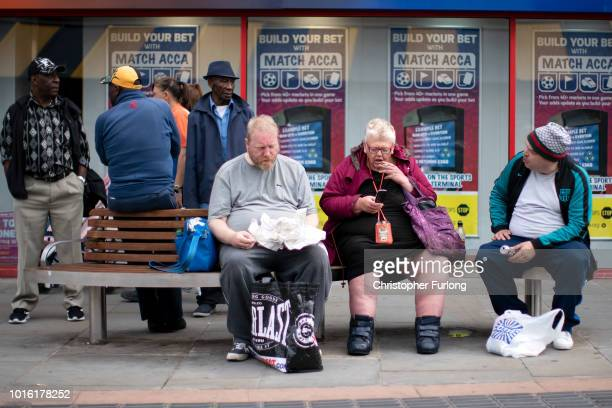 People sit after doing their shopping in the centre of town in the Black Country which was among the 29 out of 30 West Midlands voting areas to back...