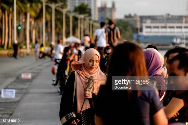 People sit along a sea wall of Manila Bay in Manila Philippines on Sunday Nov 12 2017 Economists are forecasting the Philippines to be among the...