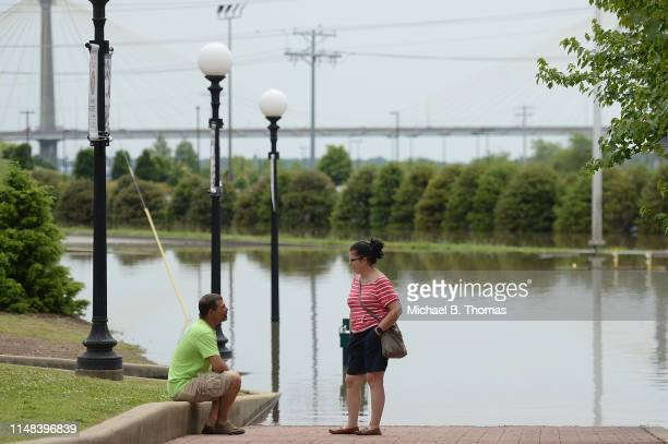People sit along a submerged road on June 6 2019 in Alton Illinois Residents along the Mississippi River are bracing for the expected arrival of the...