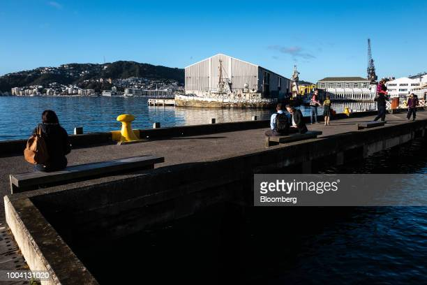 People sit along a waterfront in Wellington New Zealand on Wednesday July 18 2018 New Zealand inflation picked up in the second quarter amid higher...