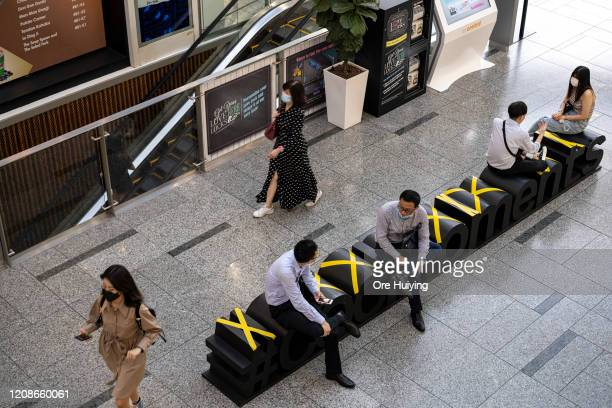 People sit along benches in The Central mall according to safe distancing markers on March 30 2020 in Singapore The Singapore government has...