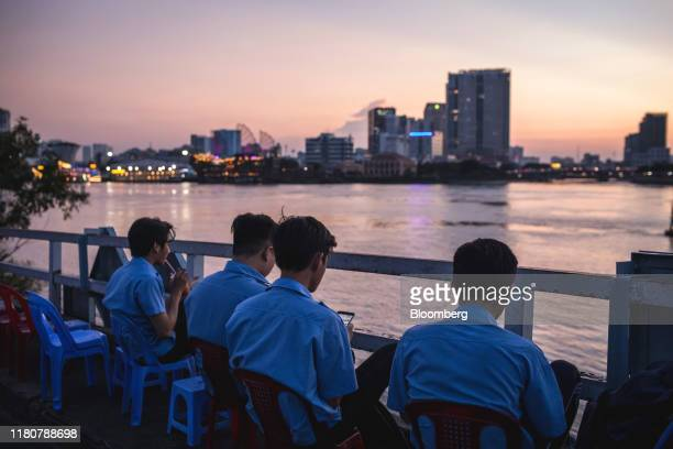People sit along the Saigon River at dusk in Ho Chi Minh city Vietnam on Wednesday Sept 11 2019 Vietnam is the seventhlargest goods exporter to the...