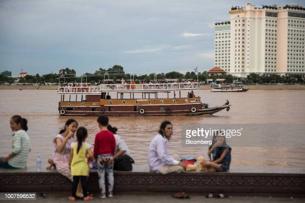 People sit along the waterfront as a cruise boat sails along the Tonle Sap River in Phnom Penh Cambodia on Sunday July 29 2018 Cambodian Prime...