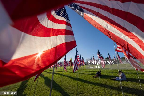 People sit among flags during the 14th annual Waves of Flags on the eve of the 20th anniversary of the September 11 terror attacks in Alumni Park at...