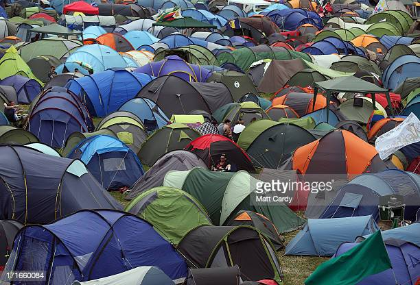 People sit amongst tents at the Glastonbury Festival of Contemporary Performing Arts site at Worthy Farm Pilton on June 27 2013 near Glastonbury...