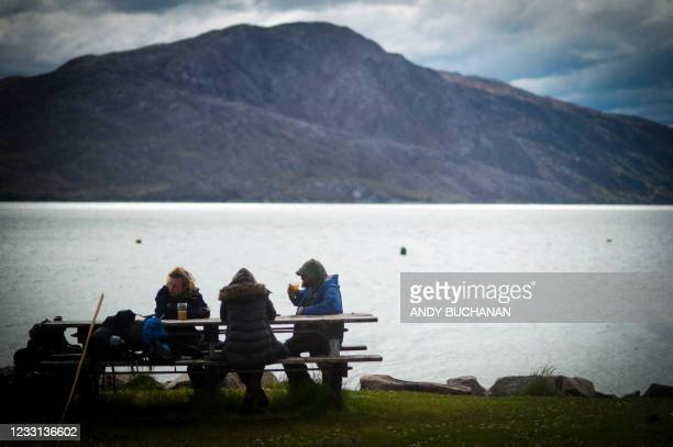 People sit and drink outside The Old Forge pub, owned by Jean-Pierre Robinet, overlooking Loch Nevis in Inverie on the Knoydart peninsular in the...