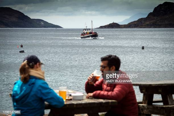 People sit and drink outside The Old Forge pub, owned by Jean-Pierre Robinet, as the the 'Western Isles' ferry crosses Loch Nevis from Mallaig as it...