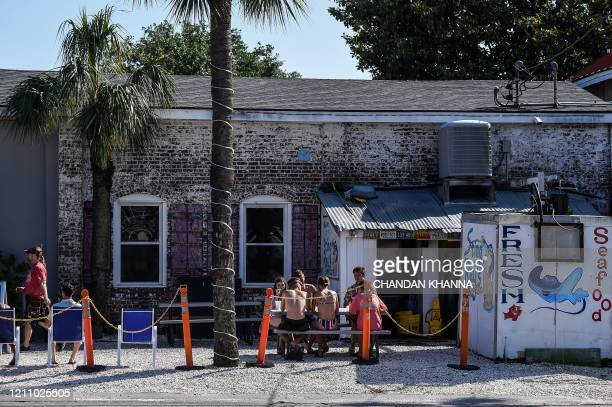 People sit and eat at a road side food joint amid the novel coronavirus pandemic in Tybee Island, Georgia, on April 25, 2020. - After being locked...