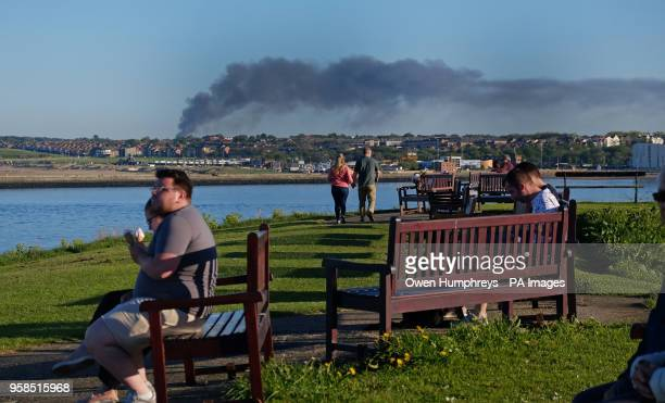 People sit and enjoy ice creams alongside the River Wear as black smoke rises from a large fire in Sunderland