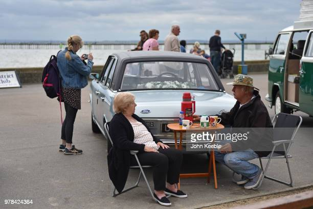 People sit and have a picnic by their Ford Cortina Mk2 during the Southend Classic Car Show along the seafront on June 17 2018 in Southend on Sea...