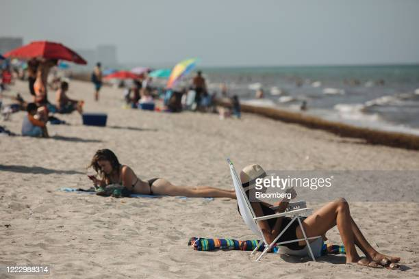 People sit and lay on the beach in Hollywood, Florida, U.S., on Thursday, June 25, 2020. On Thursday, Florida reported more than 5,000 new confirmed...
